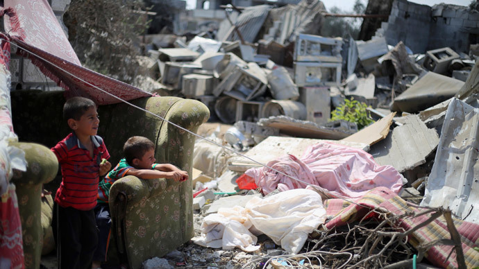 Palestinian children sit near a destroyed house in Khan Yunis in the southern Gaza Strip.(AFP Photo / Said Khatib )