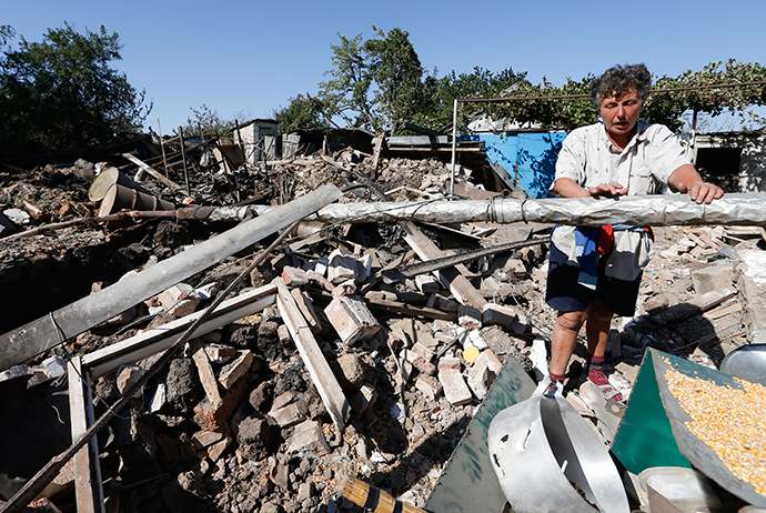 A woman stands at her destroyed house in the village of Kominternovo, on the outskirts of the southern coastal town of Mariupol, September 6, 2014 (Reuters / Vasily Fedosenko)
