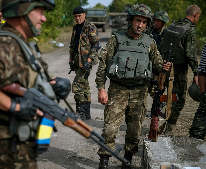 Ukrainian soldiers stand at a checkpoint near the eastern Ukrainian town of Pervomaysk September 12, 2014 (Reuters / Gleb Garanich)