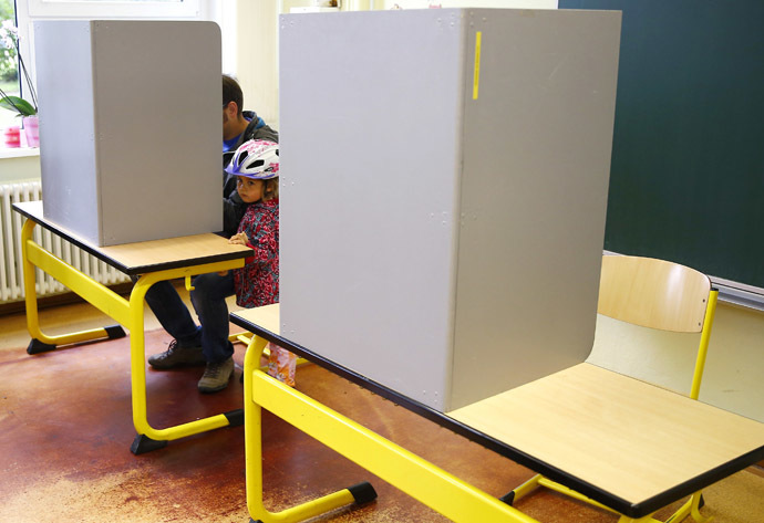 A girls stands next to her father as he casts his vote during the Thuringia state election at a polling station in a school in Erfurt September 14, 2014. (Reuters/Kai Pfaffenbach)