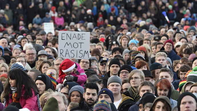 """People demonstrating against nazism and racism hold a placard reading """"united against racism"""" in the Stockholm suburb Karrtorp, Sweden on December 22, 2013. (AFP/TT News Agency)"""