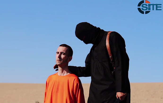An image grab taken from a video released by the Islamic State (IS) and identified by private terrorism monitor SITE Intelligence Group on September 13, 2014 purportedly shows British aid worker David Haines dressed in orange and on his knees in a desert landscape speaking to the camera before being beheaded by a masked militant (R) (AFP Photo / HO)
