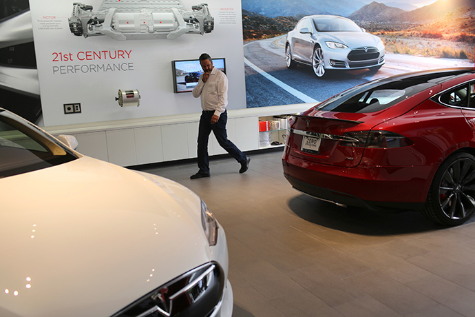 A man looks over a pair of Tesla Model S electric automobiles at a Tesla Motors showroom (Reuters / Robert Galbraith)
