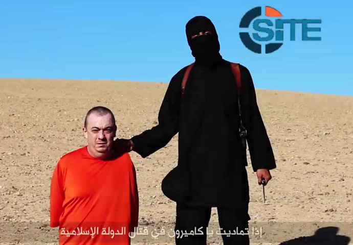 In a still taken from an IS video, uploaded to the web on Saturday, a masked jihadist warns UK hostage Alan Henning will be the terror group's next victim.(AFP Photo / Site Intelligence Group)