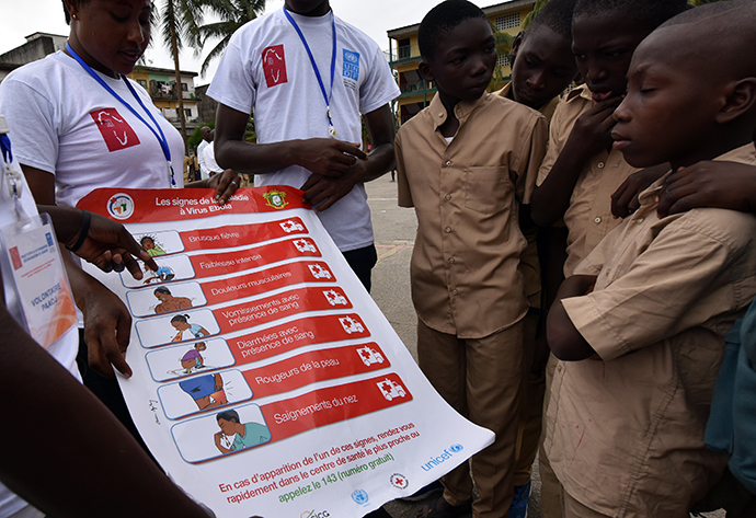 Volunteers wearing a t-shirt of the United Nations Development Programme (UNDP) show a placard to raise awareness on the symptoms of the Ebola virus to students of the Sainte Therese school, in the Koumassi district, in Abidjan (AFP Photo / Sia Kambou)