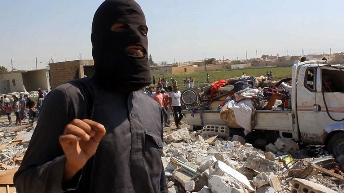 A jihadist from the Islamic State (IS) group standing on the rubble of houses after a Syrian warplane was reportedly shot down by IS militants over the Syrian town of Raqa. (AFP/AFPTV screenshot)