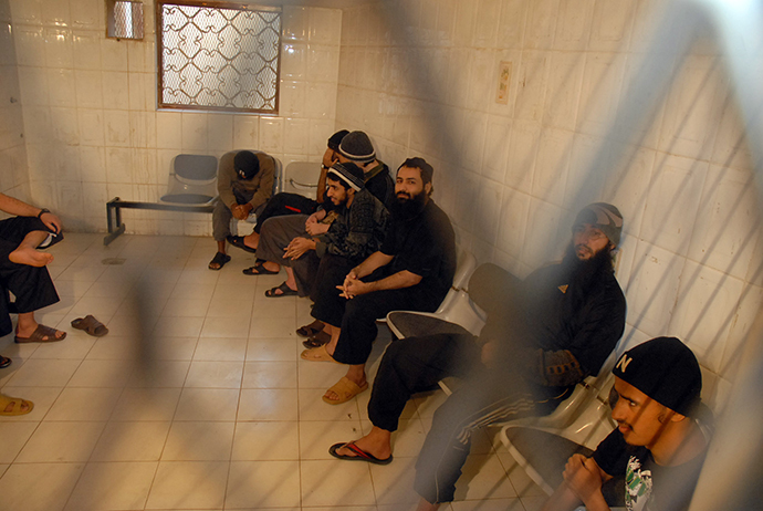 Some of the ten alleged Al-Qaeda members sit in a holding-room in court during their hearing in the Yemeni capital Sanaa (AFP Photo / Gamal Noman)