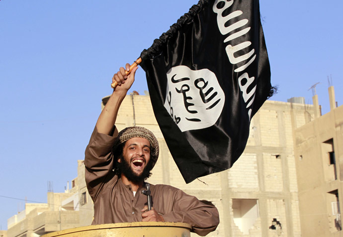 A militant Islamist fighter waving a flag, cheers as he takes part in a military parade along the streets of Syria's northern Raqqa province June 30, 2014. (Reuters)