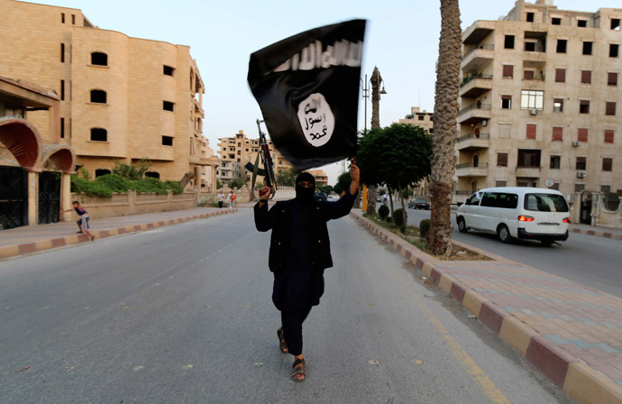 A member loyal to the Islamic State in Iraq and the Levant (ISIL) waves an ISIL flag in Raqqa (Reuters / Stringer)