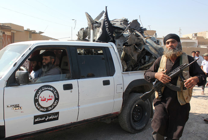 "An Islamic gunman walks past a pick up truck belonging to the ""Raqa Regional Public Service"" headed by the Islamic State (IS) group loaded with the wreckage of a Syrian government forces aircraft which was shot down by IS' militants over the Syrian town of Raqa (AFP Photo / Str)"