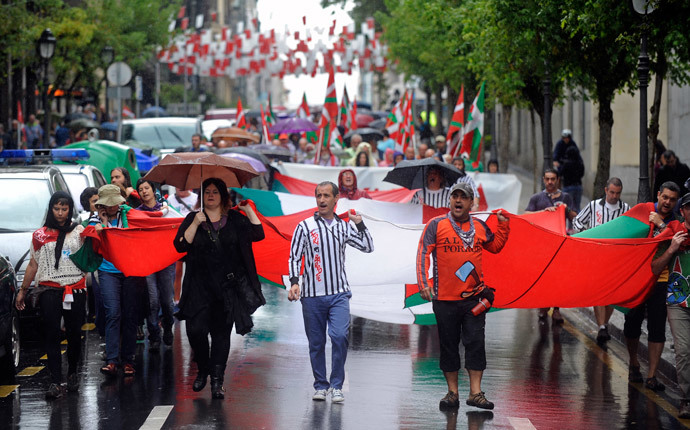 Pro independence demonstrators carry a big Ikurrina (Basque flag) as they protest in favour of the Basque flag (Ikurrina) and against the Spanish flag during the local festivities of the northern Spanish Basque city of Bilbao (AFP Photo / Rafa Rivas)