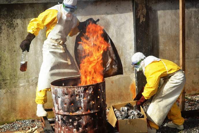 Health worker burn used protection gear at the NGO Medecins Sans Frontieres (Doctors Without Borders) center in Conakry on September 13, 2014.(AFP Photo / Cellou Binani)