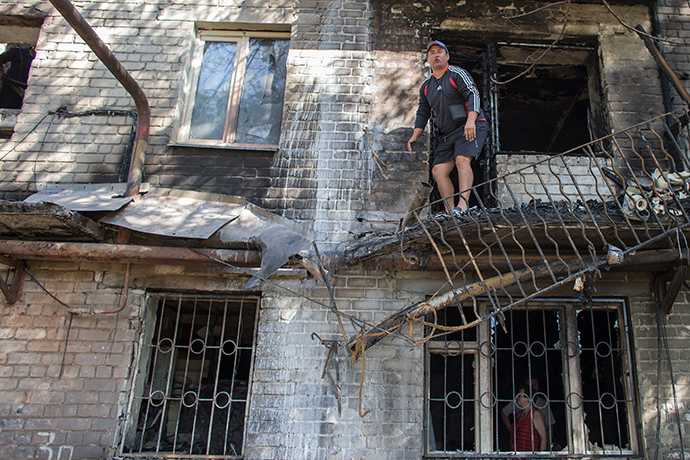 A man stands on the balcony of a building that was recently shelled in Donetsk, eastern Ukraine, September 17, 2014 (Reuters / Marko Djurica)