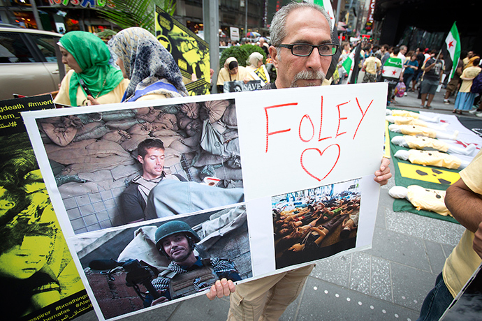 A man holds up a sign in memory of U.S. journalist James Foley during a protest against the Assad regime in Syria in Times Square in New York August 22, 2014 (Reuters / Carlo Allegri)