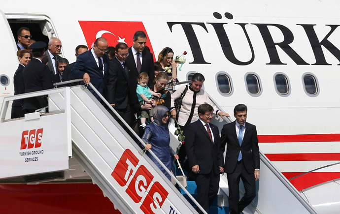 Turkey's Prime Minister Ahmet Davutoglu (C) and his wife Sare Davutoglu (L), welcome freed Turkey's Consul in Mosul Ozturk Yilmaz (R) and dozens of other freed Turkish nationals hostages held by Islamist militants in northern Iraq for more than three months, on September 20, 2014 at the Esenboga Airport in Ankara. (AFP Photo)