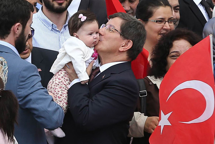 Turkey's Prime minister Ahmet Davutoglu (C) kisses the daughter of a hostage as he welcomes on September 20, 2014 in Ankara dozens of freed Turkish nationals hostages held by Islamist militants in northern Iraq for more than three months. (AFP Photo)
