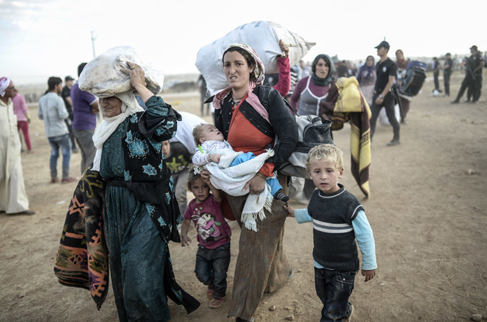 Syrian Kurds carry their belongnings near the Syrian border at the southeastern town of Suruc in Sanliurfa province, on September 20, 2014. (AFP Photo/Bulent Kilic)