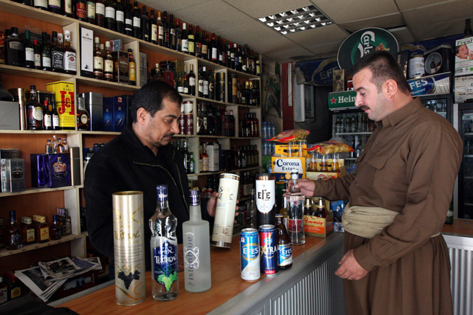 A shopkeeper displays a selection of alcoholic drinks to a Kurdish man at a store in Arbil, 310 km (190 miles) north of Baghdad (Reuters/Azad Lashkari)
