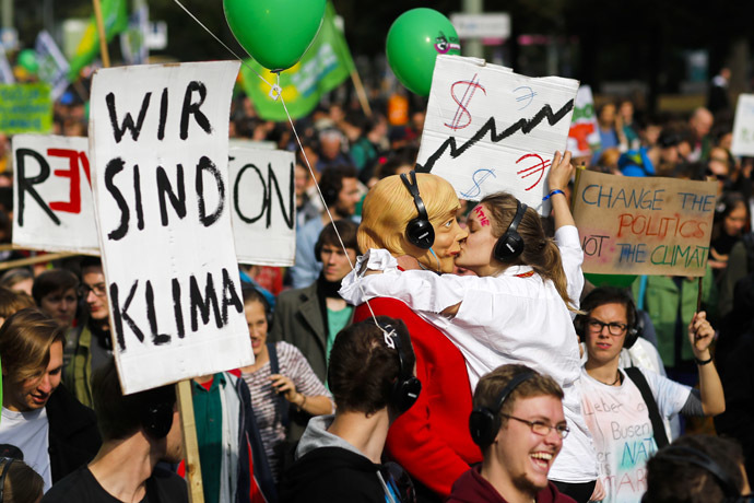 People hold banners and dance during a Climate Change March demanding politicians take tougher action to protect the climate in Berlin, September 21, 2014. (Reuters/Thomas Peter)