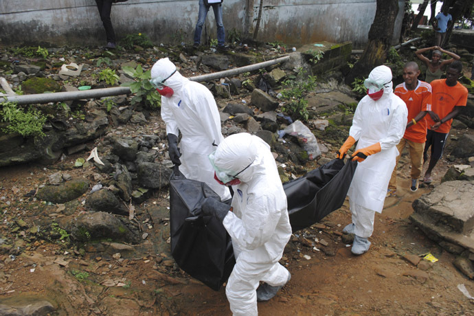 Health workers remove the body of Prince Nyentee, a 29-year-old man whom local residents said died of Ebola virus in Monrovia September 11, 2014. (Reuters/James Giahyue)