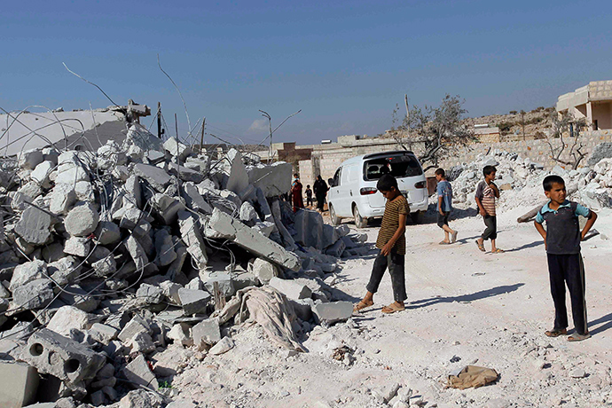Residents inspect damaged buildings in what activists say was a U.S. strike, in Kfredrian, Idlib province September 23, 2014 (Reuters / Abdalghne Karoof)