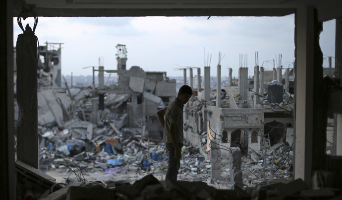 A Palestinian stands in his badly damaged house as the ruins of houses, which witnesses said were destroyed during the seven-week Israeli offensive, are seen in the east of Gaza City August 31, 2014. (Reuters/Suhaib Salem)