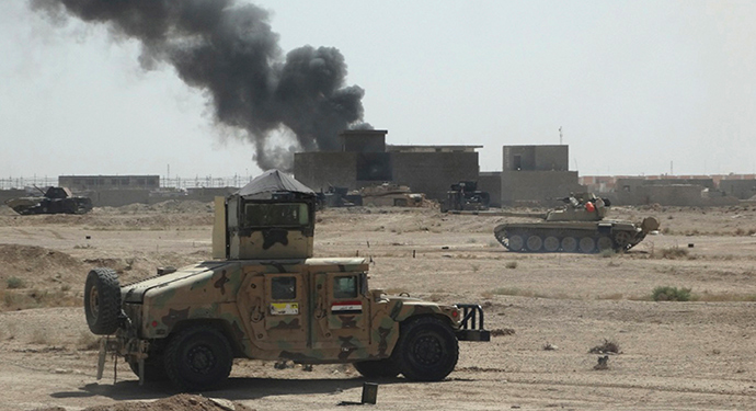 A convoy of Iraqi security forces is seen during a patrol, as smoke rises from clashes with Islamic State (IS) militants, on the outskirts of Ramadi, September 19, 2014. Picture taken September 19, 2014 (Reuters / Osama Al-dulaimi)