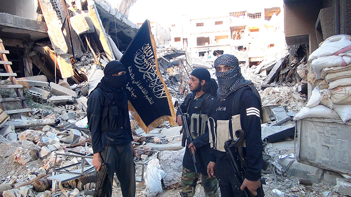Fighters from the al-Qaida group in the Levant, Al-Nusra Front, stand among destroyed buildings near the front line with Syrian government solders in Yarmuk Palestinian refugee camp, south of Damascus on September 22, 2014 (AFP Photo / HO)