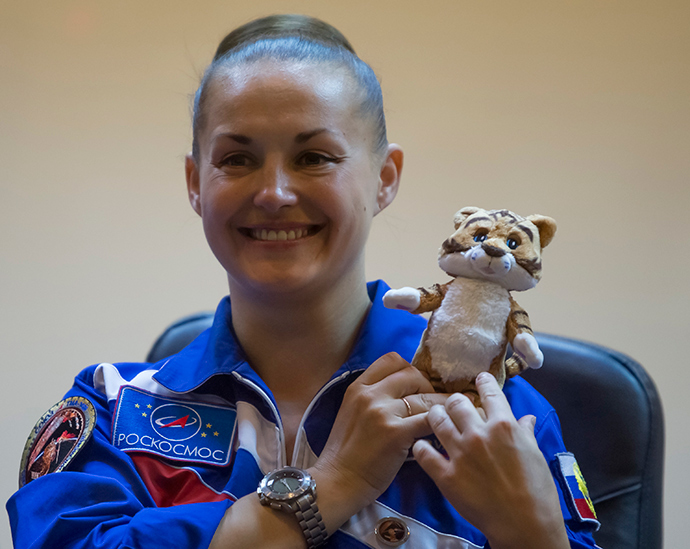 The International Space Station crew member Elena Serova of Russia holds a soft toy, that will be taken to the station, during a news conference behind a glass wall at Baikonur cosmodrome September 24, 2014 (Reuters / Shamil Zhumatov)