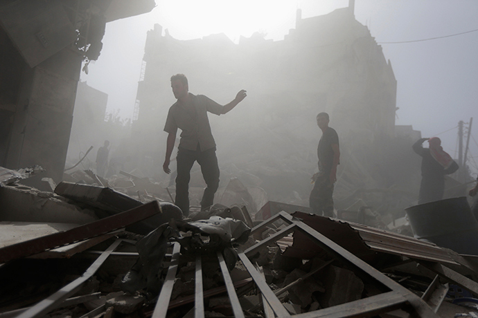 Residents inspect a damaged site after what activists say were four air strikes by forces loyal to Syria's President Bashar al-Assad in Douma, eastern al-Ghouta, near Damascus September 24, 2014 (Reuters / Bassam Khabieh)