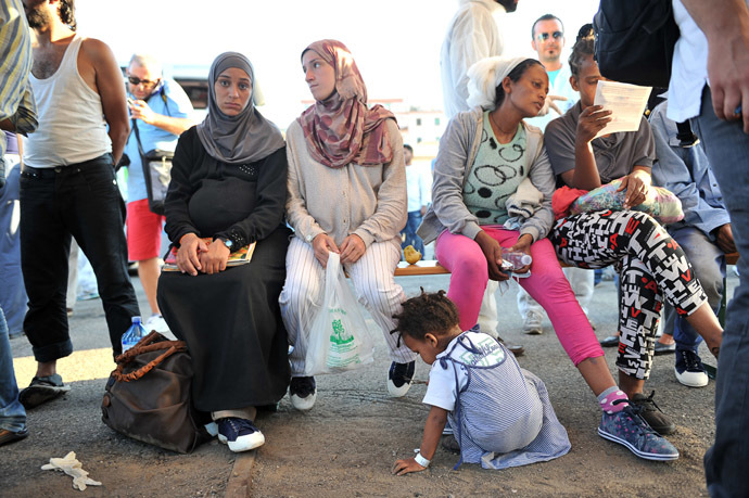 "Immigrants, part of a group of more than 1,370 people, wait after they disembarked from the Italian military ship ""San Giusto"" on August 25, 2014. (AFP Photo/Alfonso Di Vincenzo)"