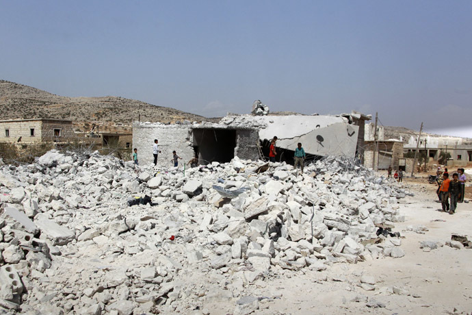 Residents look at buildings which were damaged in what activists say was one of Tuesday's U.S. air strikes in Kfredrian, Idlib province September 24, 2014. (Reuters/Ammar Abdullah)