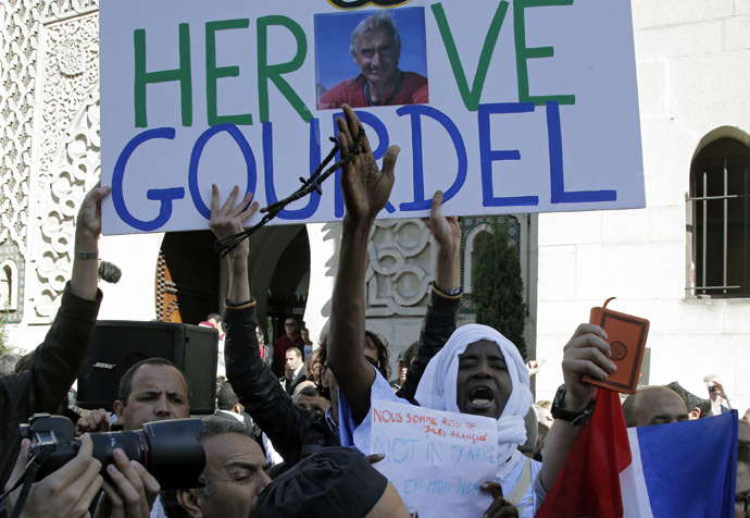 "A man holds a placard which reads ""Homage to Herve Gourdel"", a French mountain guide who was beheaded by an Algerian Islamist group, during a gathering of Muslims in front of the Paris Mosque after Friday prayers September 26, 2014. (Reuters/Jacky Naegelen)"