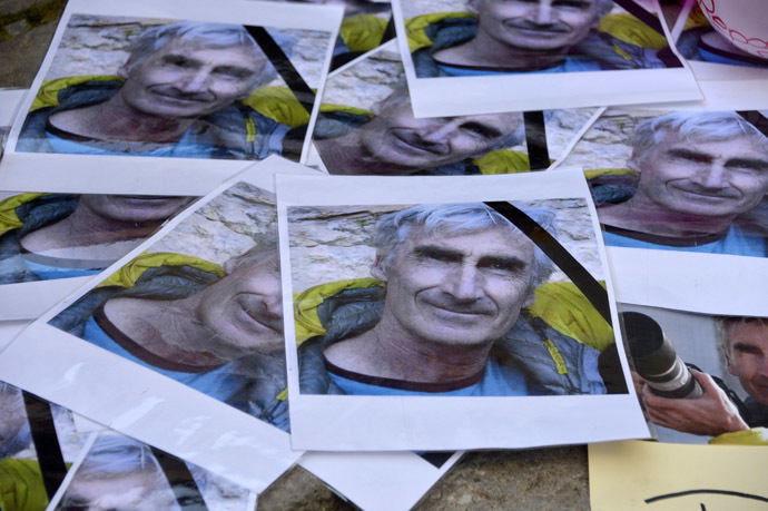 Portraits of mountain guide Frenchman Herve Gourdelin are seen as people pay tribute in Saint-Martin-Vesubie, September 25, 2014. (Reuters/Patrice Masante)