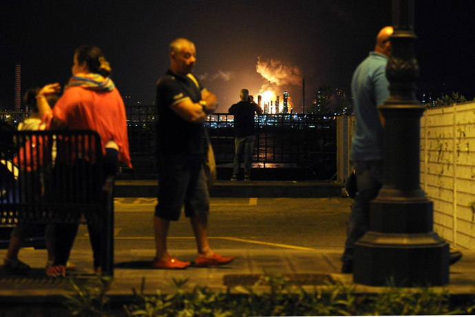 People stand as flames arise after a fire broke out at the Mediterranean Refinery of Milazzo, one of most important in southern Italy, in Milazzo, near Messina on Sicily Island on September 27, 2014. (AFP Photo/Giovanni Isolino)