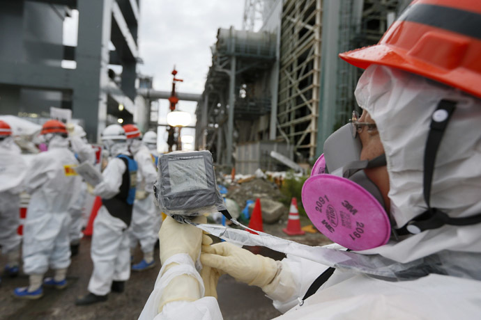 A Tokyo Electric Power Co. (Tepco) employee measures radiation levels as workers conduct operations to construct an underground ice wall at Tepco's tsunami-crippled Fukushima Daiichi nuclear power plant in Fukushima Prefecture July 9, 2014. (Reuters/Kimimasa Mayama)