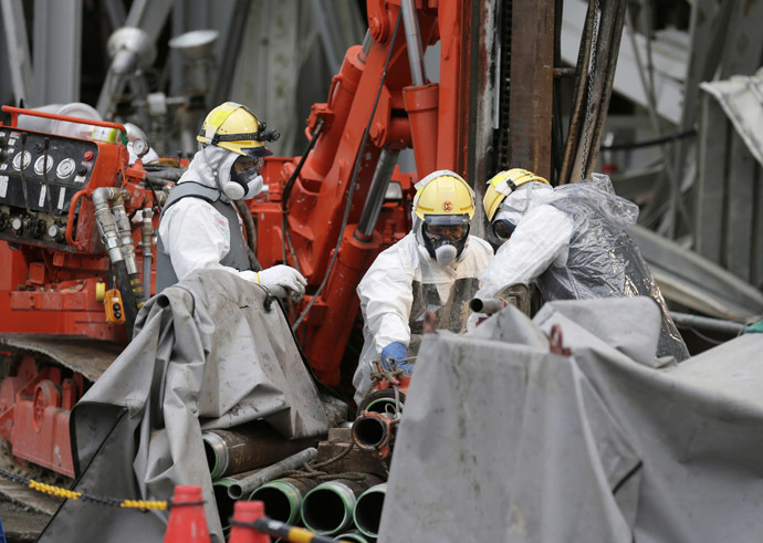 Workers conduct operations to construct an underground ice wall at Tokyo Electric Power Co.'s (Tepco) tsunami-crippled Fukushima Daiichi nuclear power plant in Fukushima Prefecture July 9, 2014. (Reuters/Kimimasa Mayama)