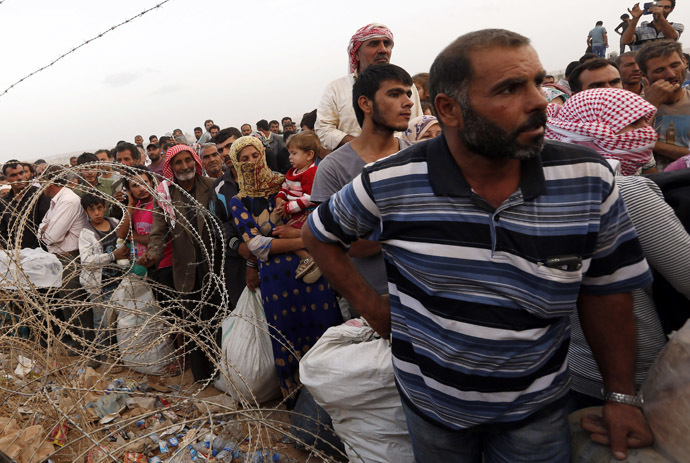 Syrian Kurdish refugees wait behind the border fences to cross into Turkey near the southeastern town of Suruc in Sanliurfa province September 27, 2014. (Reuters/Murad Sezer)