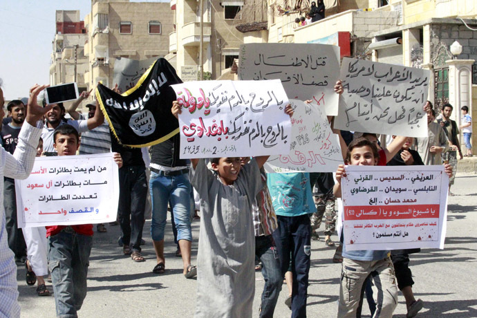 "RYouths carry banners during a protest against the U.S. airstrikes on the Islamic State (IS) in Raqqa September 26, 2014. The banners in Arabic read, ""By the soul, by the blood, we sacrifice ourselves oh state. by the soul, by the blood, we sacrifice ourselves oh Baghdadi"" (C),""Who did not die by Assad's planes, died by Saudi family planes, The planes became many, but the strikes are one"" (L). (Reuters)"
