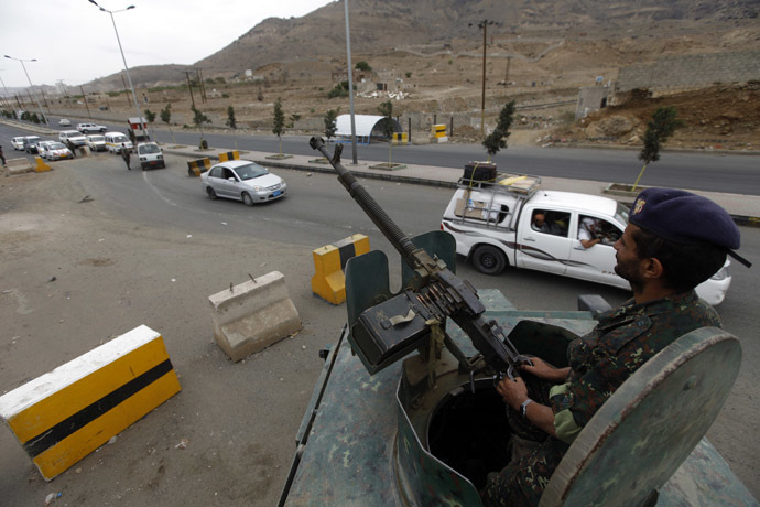 A soldier sits on top an armoured military vehicle as he mans a checkpoint near the U.S. embassy in Sanaa (Reuters/Mohamed al-Sayaghi)