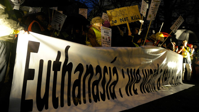 "Protesters, who call themselves the ""yellow jackets"", hold banners and placards as they demonstrate against a new law authorizing euthanasia for children, in Brussels.(Reuters / Laurent Dubrule)"