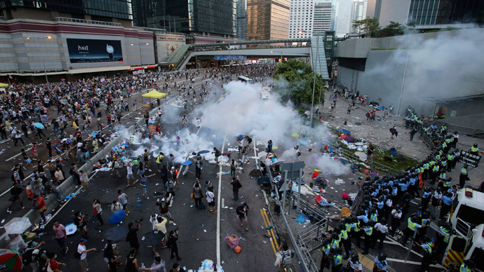 Riot police fire teargas to disperse protesters, during clashes after thousands of protesters blocked the main street to the financial Central district (background) outside the government headquarters in Hong Kong September 28, 2014.(Reuters / Stringer)