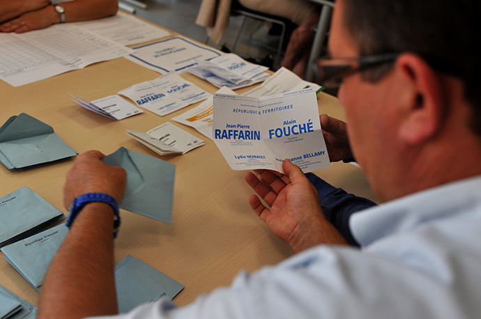 A man holds a vote for the former Prime Minister and opposition UMP party senator Jean-Pierre Raffarin during the senatorial election's vote counting, on September 28, 2014 in Poitiers. (AFP Photo / Guillaume Souvant)