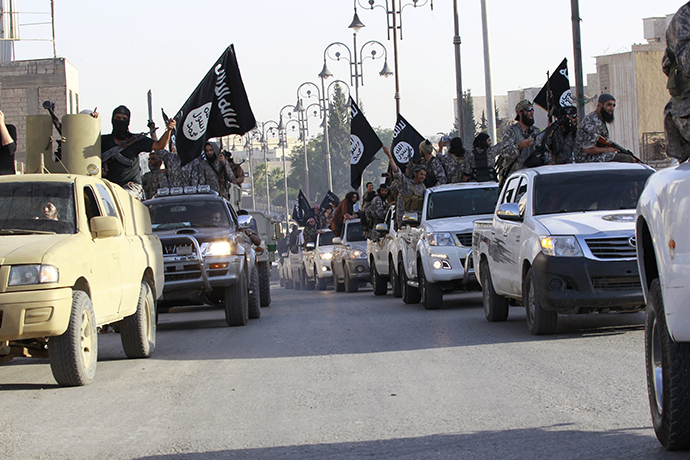 Militant Islamist fighters parade on military vehicles along the streets of northern Raqqa province (Reuters / Stringer)