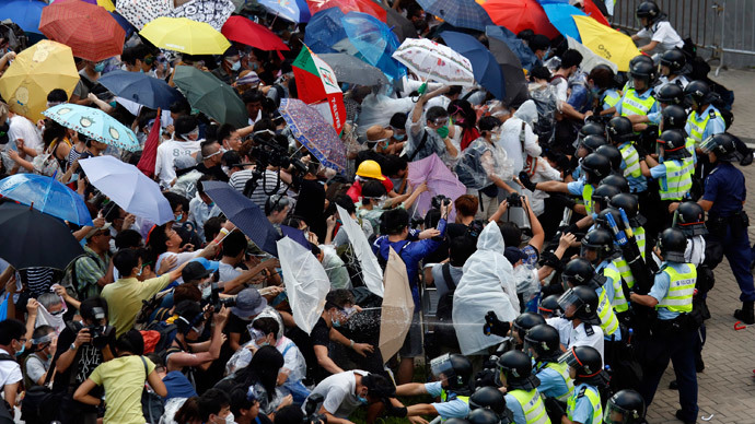 Protesters take cover from pepper spray with umbrellas as riot police clash with tens of thousands of protesters blocking the main street leading to the financial Central district outside the government headquarters in Hong Kong September 28, 2014.(Reuters / Bobby Yip)