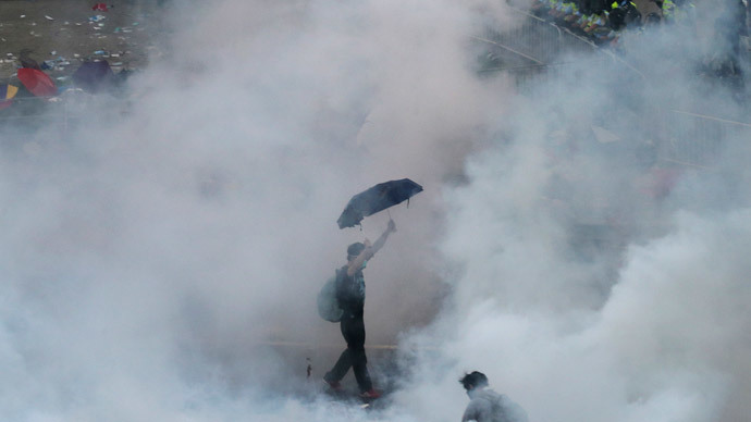 A protester walks in tear gas fired by riot policemen after thousands of protesters blocking the main street to the financial Central district outside the government headquarters in Hong Kong September 28, 2014.(Reuters / Stringer )