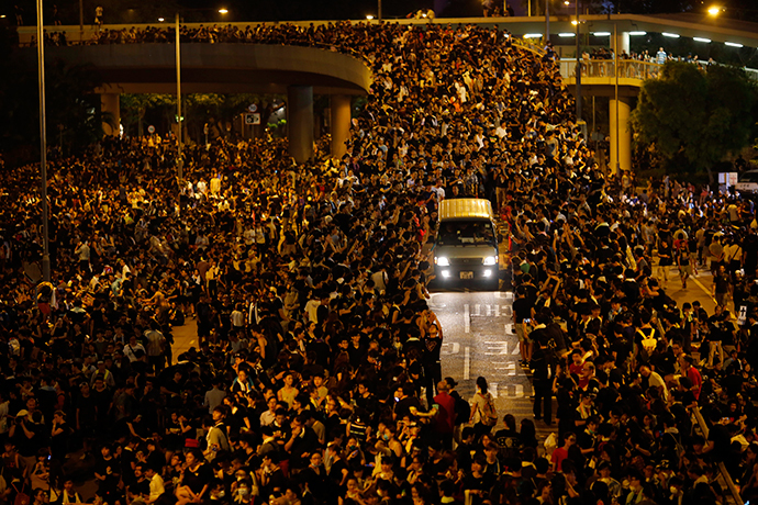 A vehicle drives among protesters blocking the main street to the financial Central district, outside the government headquarters, in Hong Kong September 29, 2014. (Reuters / Carlos Barria)