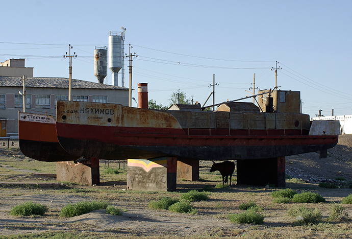 A cow takes shade in the shadow of a derelict boat in the former Aral Sea port of Aralsk, June 24, 2008 (Reuters / Aziz Mamirov)