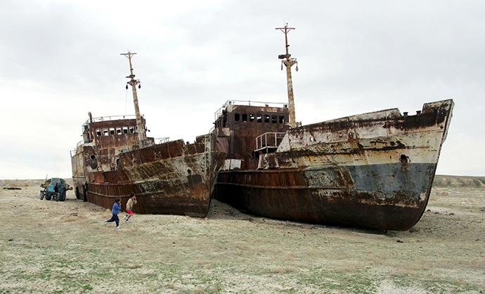 Children run past ruined ships abandoned in sand that once formed the bed of the Aral Sea near the village of Zhalanash, in southwestern Kazakhstan (Reuters / Shamil Zhumatov / Files)