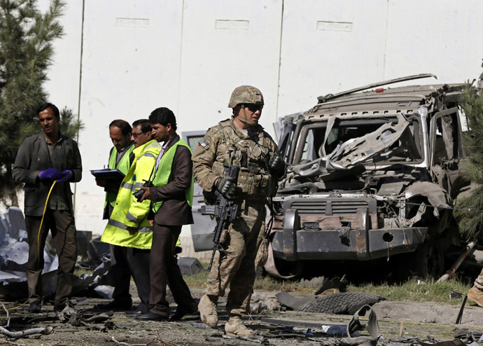 A U.S. soldier and local men carry out an investigation at the site of a suicide attack in Kabul September 16, 2014. (Reuters/Omar Sobhani)